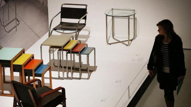 """Visitante observa mesas e cadeiras expostas na exibição """"Bauhaus Arte como Vida"""" em Londres"""