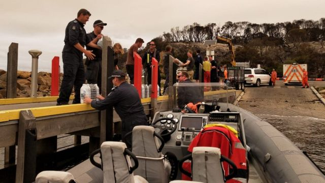 Police unloading water in Mallacoota from one of their smaller vessels