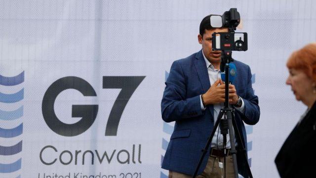 صحفي يقف وخلفه شعار مجموعة السبع
