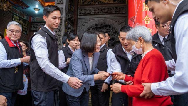 President Tsai Ing-wen distributes a red envelope to an old woman.