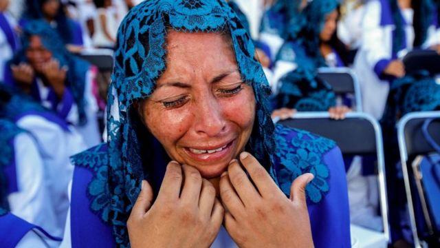 Una seguidora de la iglesia La Luz del Mundo llora durante una misa.