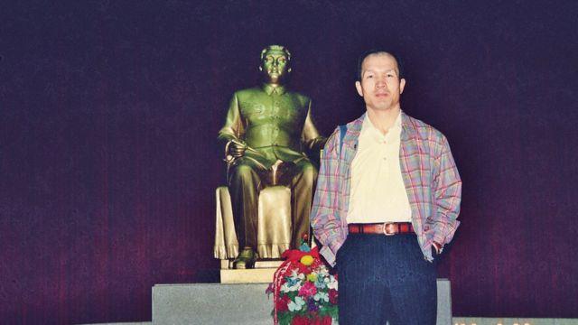 Park em pé na frente de uma estátua de Kim Jong-il em Pyongyang em 1997