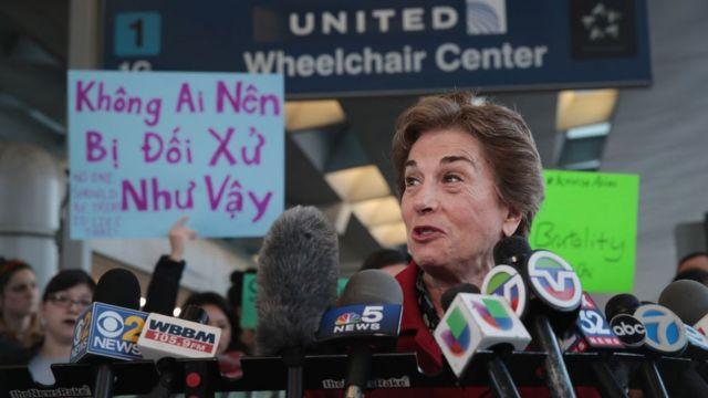 Congresswoman Jan Schakowsky speaks in front of a protester's sign, written in Vietnamese