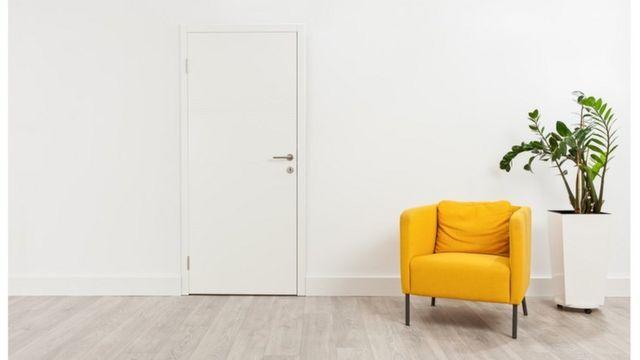 Un sofá amarillo y una planta en un espacio mayormente blanco