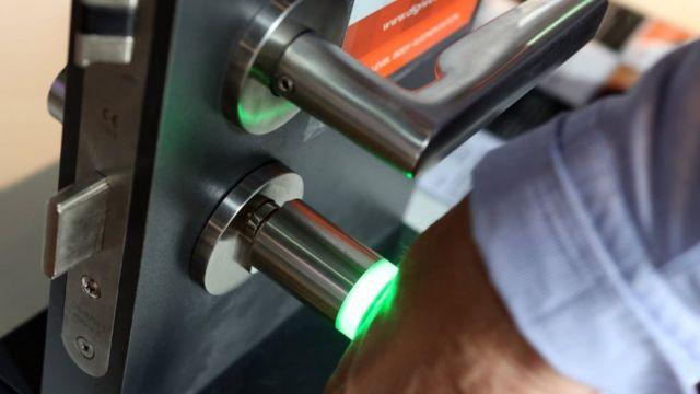 Человек открывает дверь с помощью микрочипа в руке