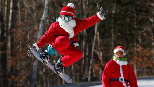 A snowboarder dressed as Santa