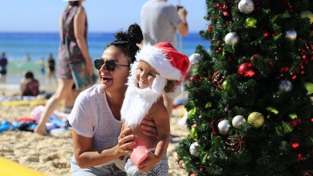 Families pose by a Christmas tree on Bondi Beach on December 25, 2018