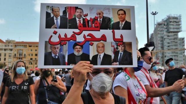 """یک معترض عکس روسای احزاب سیاسی در لبنان را بالا گرفته و روی آن نوشته """"مجرمان"""""""