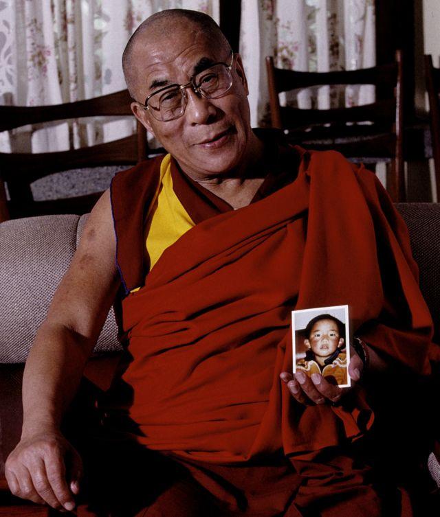Dalai Lama segurando uma foto de Gedhun Choekyi Nyima quando ele tinha 6 anos