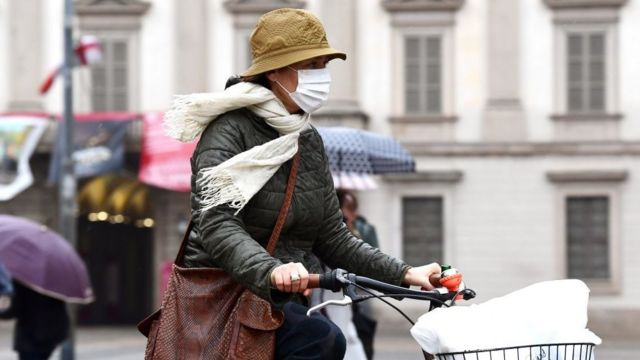 سيدة تقود دراجة وتضع كمامة للوقاية