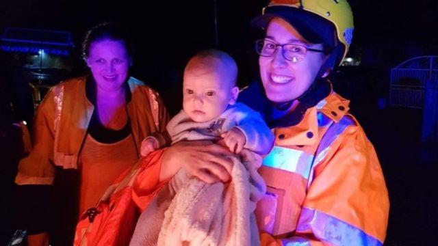 Pekerja layanan darurat menggendong bayi yang diselamatkan selama banjir Sydney