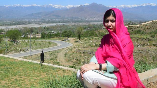 Malala Yousafzai, sentada em frente à paisagem de sua terra natal