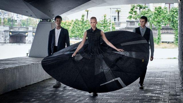 Dançarinos do Dutch National Ballet, um deles com um tutu gigante, caminham