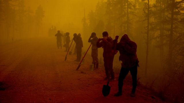 Workers cover themselves in smoke from fires in Yakutsk, Russia.