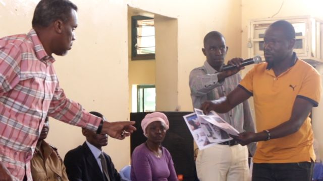 Wilfred Olal hands over print outs to the state prosecutor Noordin Haji (l)