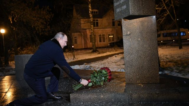 President Putin placing flowers on a grave.