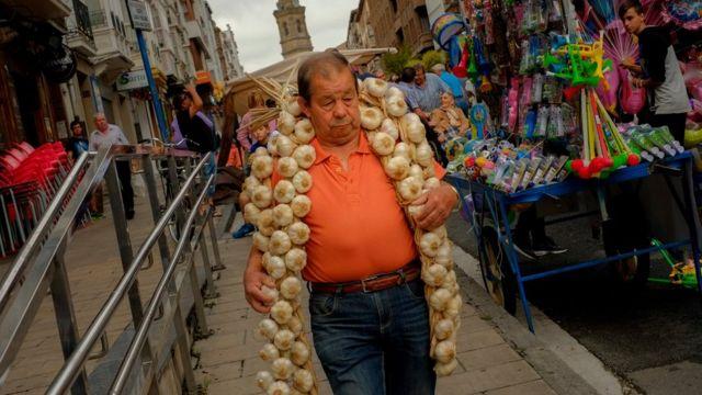 Un hombre con una ristra de ajos en una calle de España.