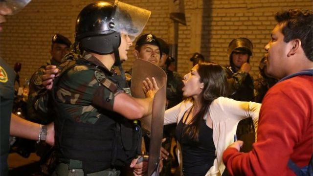 元大統領の入院先に向かおうとするデモ隊と阻止する警察(25日、リマ)