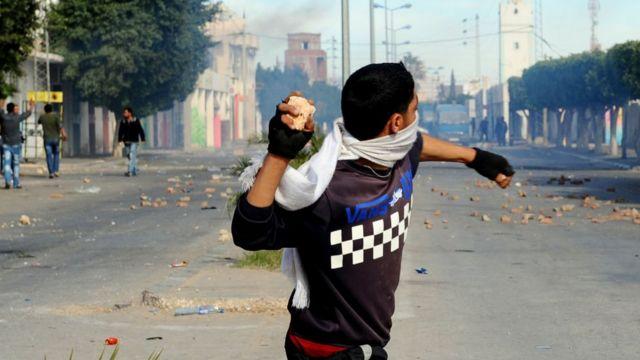 Um jovem atira uma pedra em uma rua cheia de fumaça