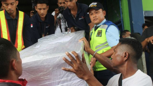 Ambrosius Koa (kanan), kerabat Adelina Sau, membantu petugas bandara mengangkut peti mati yang membawa jenazah Adelina saat tiba di Bandara Kupang, Nusa Tenggara Timur, pada 17 Februari 2018.