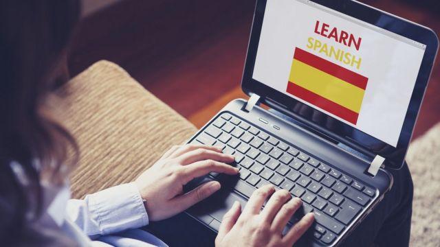 Una persona frente a una computadora para aprender español.