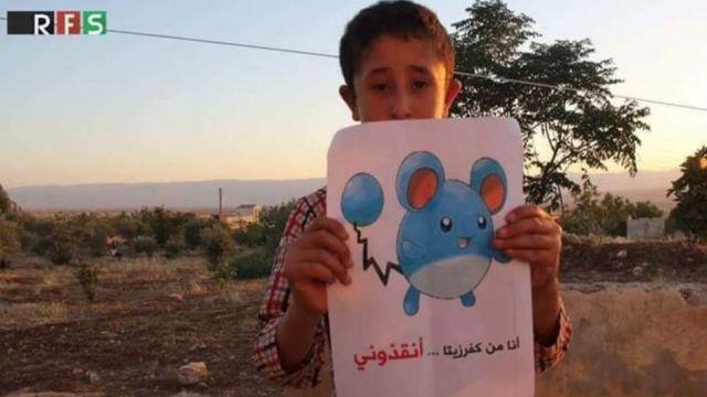 この絵のキャプションでは、ハマ県の反体制派支配地域にいるこの少年が助けを求めている