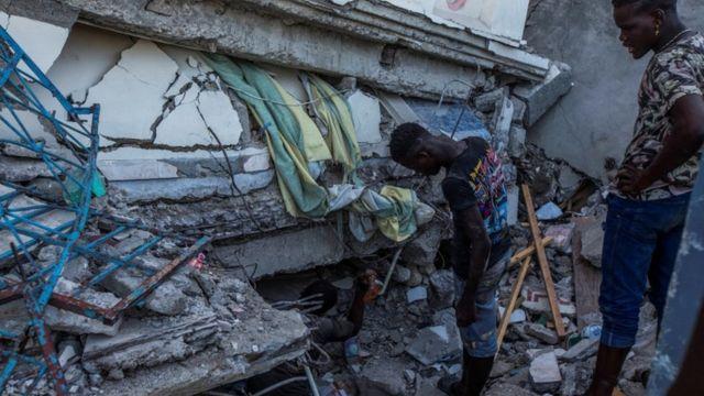 I residenti di Le Cayes guardano una casa crollata.