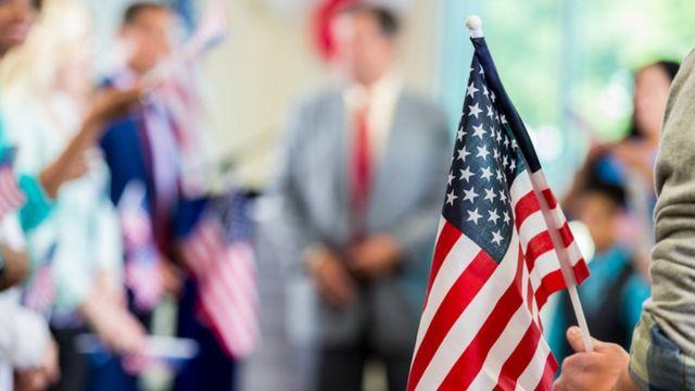 Bandera estadounidense con gente de fondo.