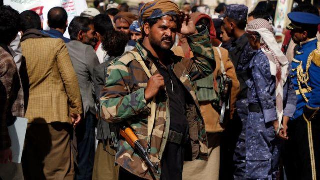 مسلح يمني أمام جمع من الناس
