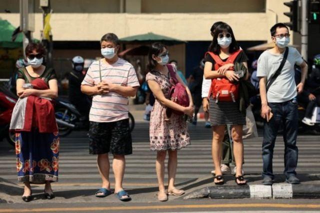 Sejumlah turis China mengenakan masker saat berwisata di kawasan keramaian kota Bangkok, Thailand.