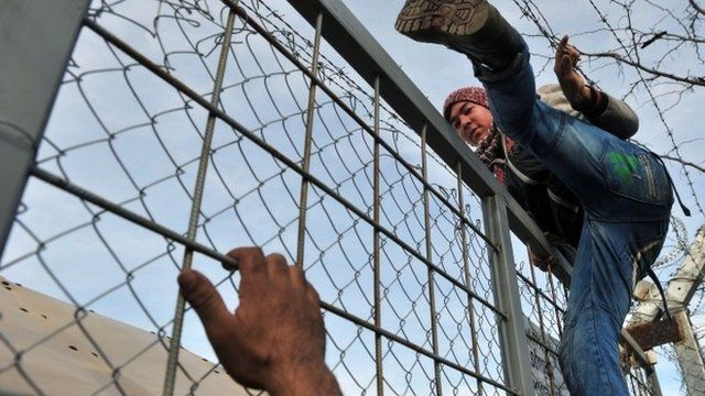 A man climbs over a fence of the Greek-Macedonian border near the village of Idomeni, northern Greece