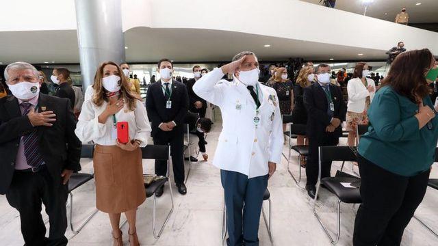 Médicos de máscara em pé, perto de cadeiras enfileiradas, um deles prestando continência