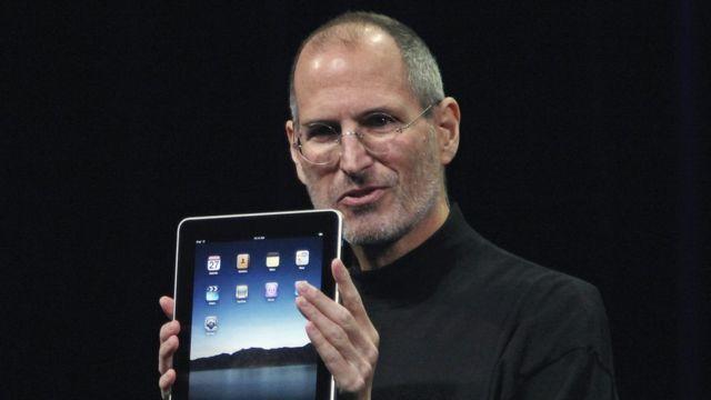 Steve Jobs segura um iPad em evento de apresentação da Apple