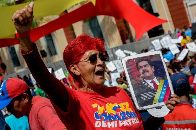Una mujer con un retrato de Maduro