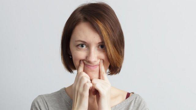 Mujer fingiendo una sonrisa