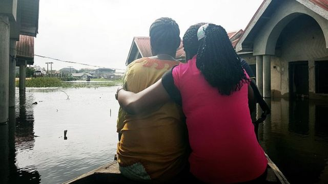 LAGOS, NIGERIA - OCTOBER 7: A couple is seen on a boat after the Ogun region flooded following a day long torrential rain caused Ogun river to overflow in Lagos, Nigeria on October 7, 2016.