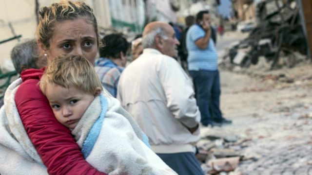A woman holds a child in Amatrice (24 August)