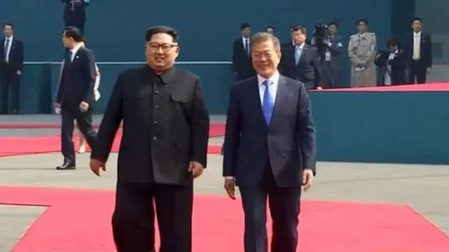 Screengrab of Reuters feed of Kim Jong-un and Moon Jae-in walking on the red carpet to Peace House