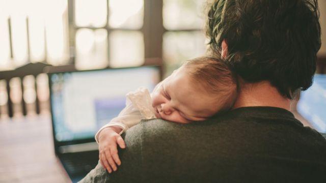 Un padre carga a un bebé mientras trabaja.