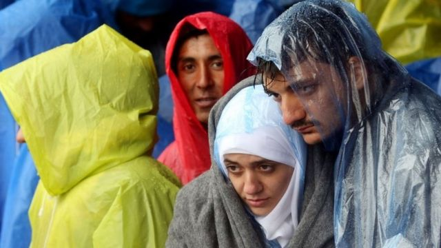 Migrants wait in the rain as they wait to enter Slovenia, at the Croatian-Slovenian border in Trnovec, on 19 October.