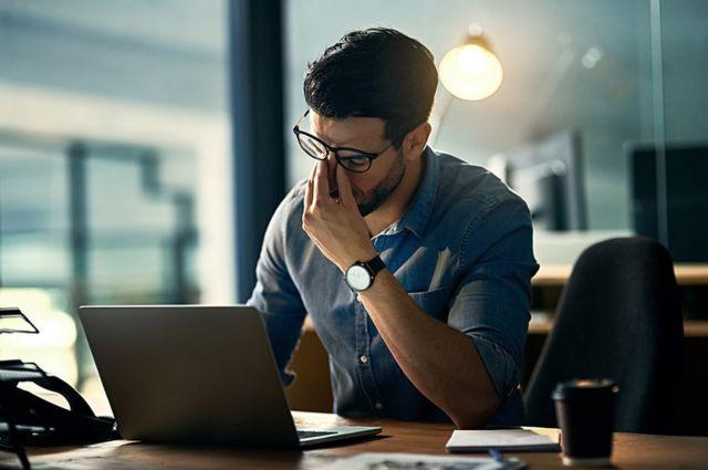Homem exausto em frente a um laptop