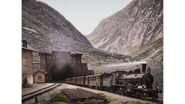 Un tren de vapor saliendo de un túnel, en medio de las montañas suizas, foto tomada en 1901. Swiss Cameera Museum Collections