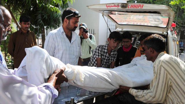 পাকিস্তানে মদ পানে মৃত একজনকে গাড়িতে উঠানো হচ্ছে