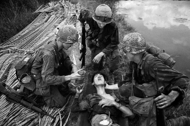 American soldiers treat an injured Vietnamese soldier