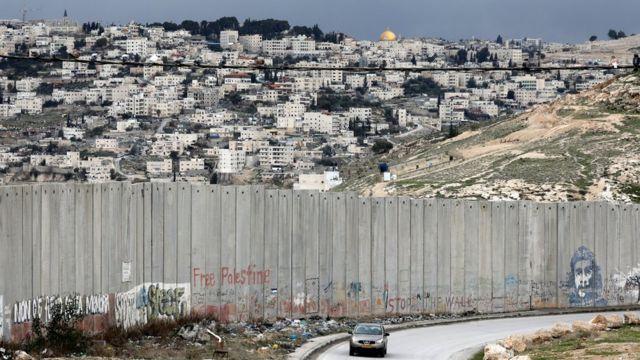 Carro passa por muro israelense na cidade palestina de Abu Dis, com Jerusalém ao fundo