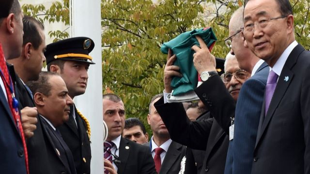 Mahmoud Abbas raises a folded Palestinian flag at UN headquarters in New York (30 September 2015)