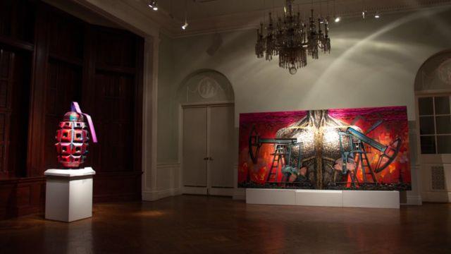 """Другие экспонаты инсталяции """"Пять элементов войны"""" - скульптура в виде гранаты и картина и изображенным торсом, выложенным из гальз"""