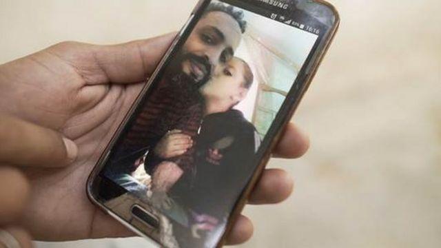 Uma mão segura um telefone com uma foto de Nidhal Gharibi
