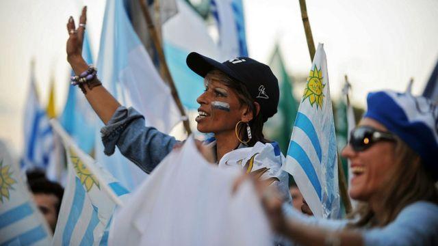 Mujer rodeada de banderas de Uruguay