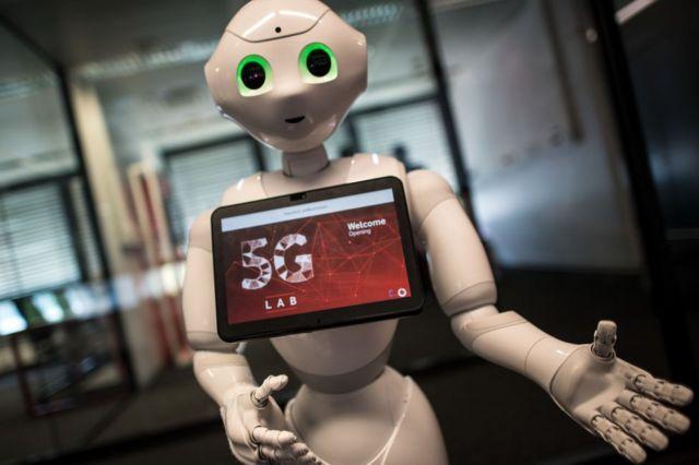 Le robot Poivre avec le logo de la 5G sur écran publicitaire